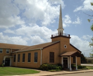 Front chapel and side office entries in this photo taken from Frio St.